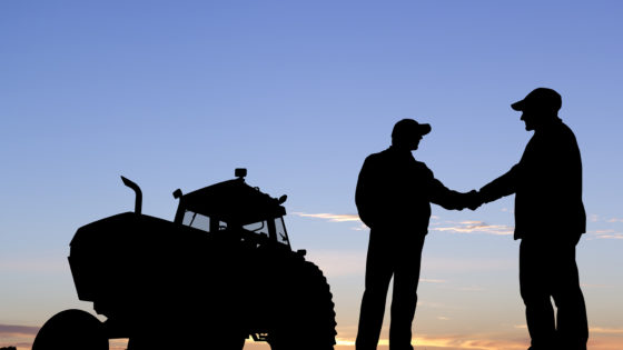 A royalty free image from the farming industry of two farmers shaking hands in front of a tractor.